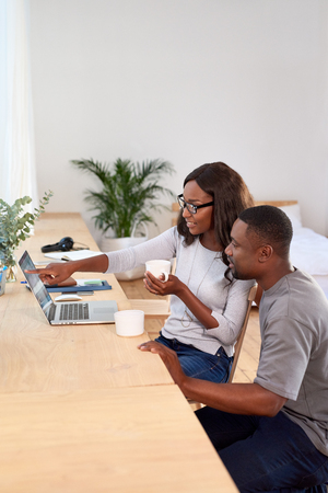 woman working from home laughs and points at computer screen while discussing ideas with husband partner man Reklamní fotografie