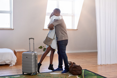 Black couple checking out their holiday rental apartment, hug and happy to be on vacation honeymoon together
