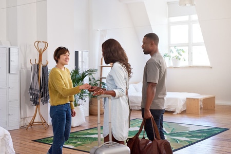 Asian woman welcomes black couple into her house home accommodation for their holiday vacation trip photo
