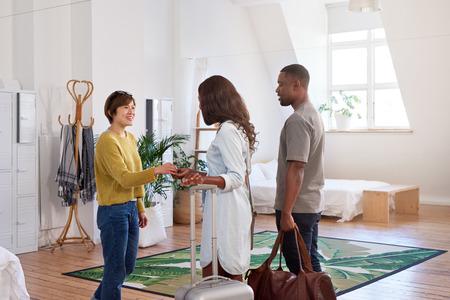La mujer asiática da la bienvenida a la pareja negra en su casa, alojamiento en casa para su viaje de vacaciones Foto de archivo