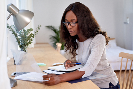 Woman working with financial graphs and paperwork from home