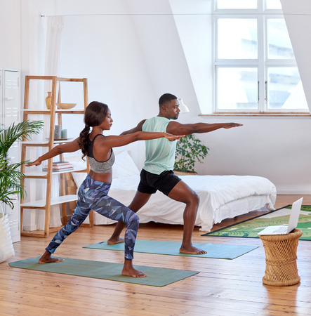 Young attractive couple practising yoga stretching workout at home, healthy lifestyle body care
