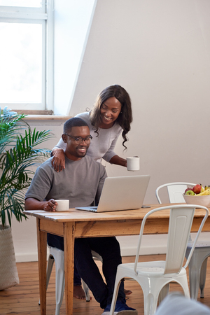 Black african woman gives husband coffee and a kiss while he works on laptop computer, sits down for a chat