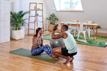 Couple in sporty athletic clothing exercising, woman planking man encouraging high five when she finishes completes training set