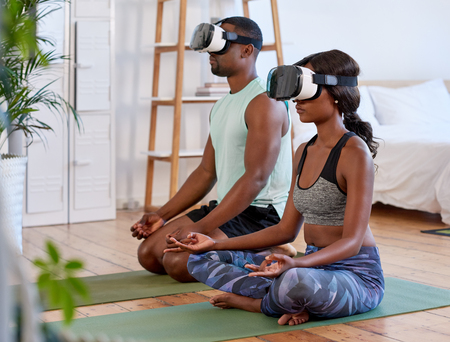 Calm relaxed couple meditating at home, VR goggles transporting them to nature modern lifestyle