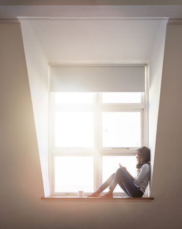Woman sitting in window seat of modern  loft city apartment using phone