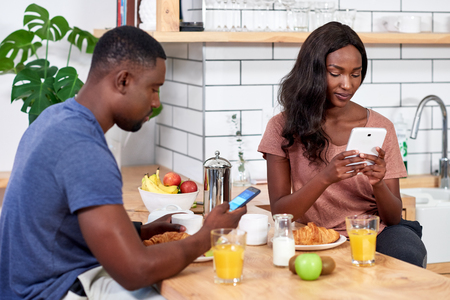 Couple at home eating breakfast and using phones and tablets to check social media Reklamní fotografie