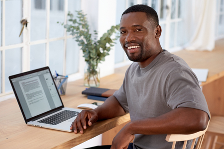 Successful black business man smiling to camera while working from home, modern working structure