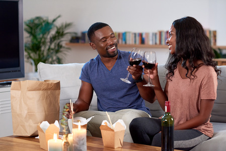 Couple enjoying food delivered by takeout app modern dining in and romantic date night Stockfoto