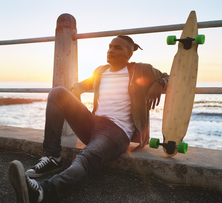 Man relaxing on walkway after longboarding skateboarding, sunset golden sun flare active outdoors lifestyle