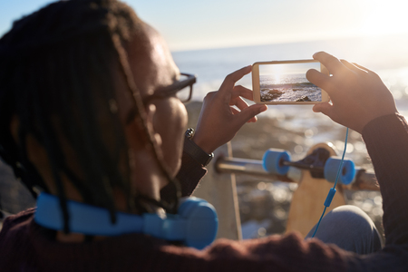 Trendy young man with dreadlocks taking photo of sunset on his mobile cell phone, beautiful scenary while skateboarding