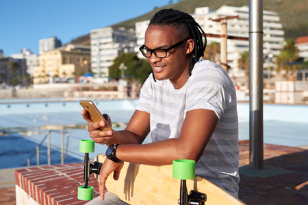Man with longboard smiling and texting on mobile cell phone, sunny summer day