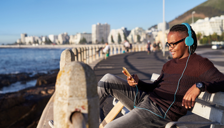 Young mixed race man selecting music playlist on his mobile cell phone, enjoying the sunset along the ocean