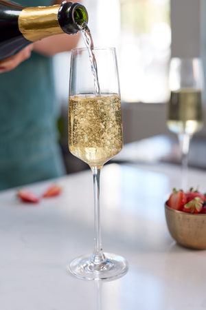 Champagne pouring, bubbles filling crystal glass party festive season holiday celebration