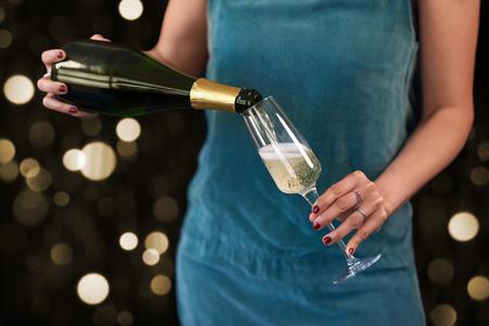 De vrouw giet champagne bij de de mousserende wijnbellen van de nieuwjarenvooravond, gouden bokeh feestelijk seizoen Stockfoto