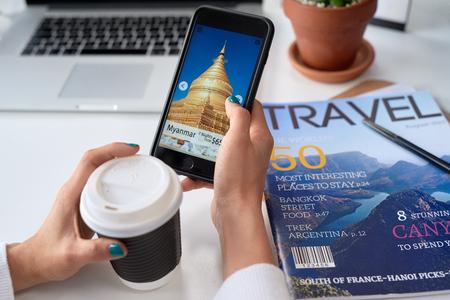 Mujer buscando ofertas de vacaciones ideas de vacaciones de destino en la aplicación de aplicaciones de viajes en el teléfono celular móvil Foto de archivo