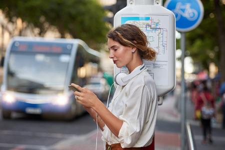 Kobieta na przystanku autobusowym z aplikacją telefonu na słuchawki muzyczne w mieście Zdjęcie Seryjne