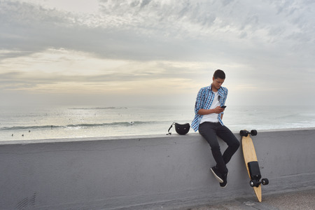 Man with electric skateboard at the beach Banco de Imagens