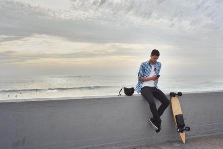 Uomo con skateboard elettrico in spiaggia