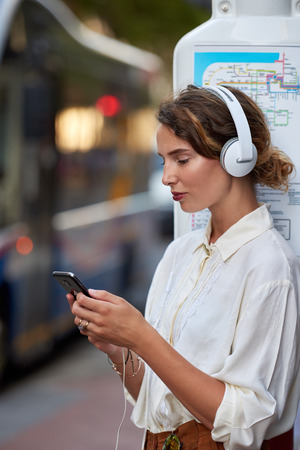 Woman at bus stop with phone app for music headphones in city 版權商用圖片 - 116944269