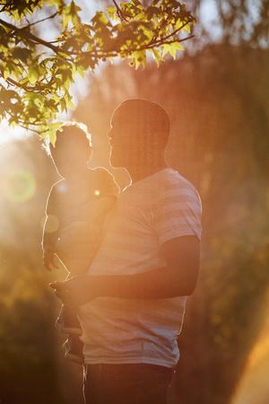 Liebender Vater, der seinen Sohn trägt und umarmt und einen Spaziergang im Park genießt, enger Bindungsmoment Standard-Bild