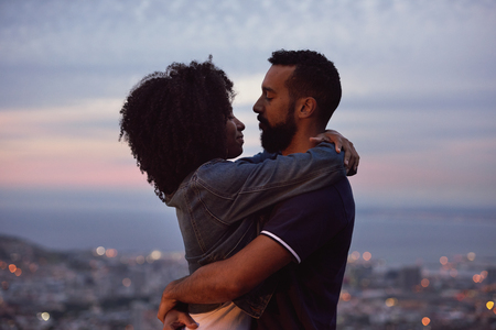 Young woman with afro hugging her boyfriend with twinkling lights of cityscape below, couple in love