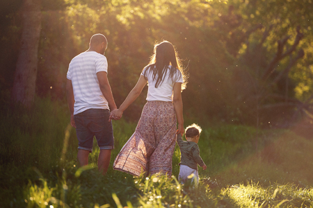 backview of family walking together in a park with young child, closeness happy together Stok Fotoğraf