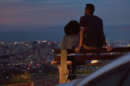 Backview of couple looking down at the city from viewpoint, enjoying the cityscape scenery Banco de Imagens