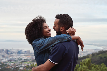 Romantic moment between couple while on holiday viewpoint overlooking foreign city