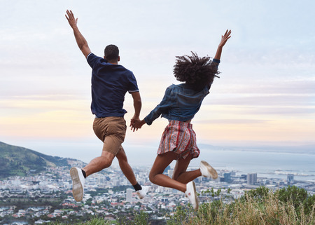 Couple holding hands and jumping in the air with raised arms excited to be on holiday viewpoint overlooking foreign city Stock Photo