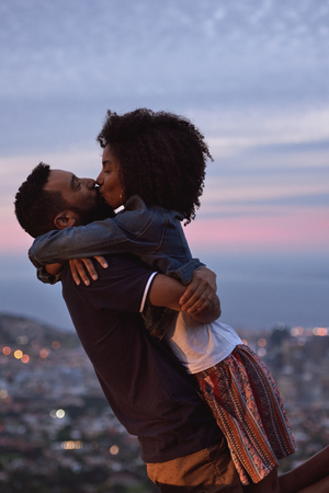 Young carefree romantic love affair, loving couple kissing at sunset with city lights