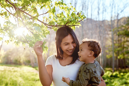 Smiling woman showing teaching her son new spring leaves about nature, mother and child closeness moment