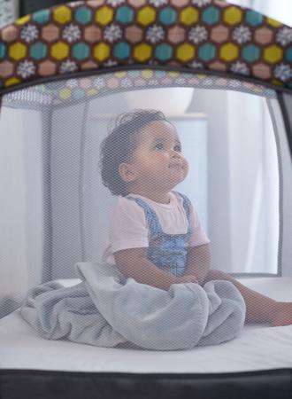 Porträt eines süßen Babys, das im Kinderbett sitzt und nach oben schaut