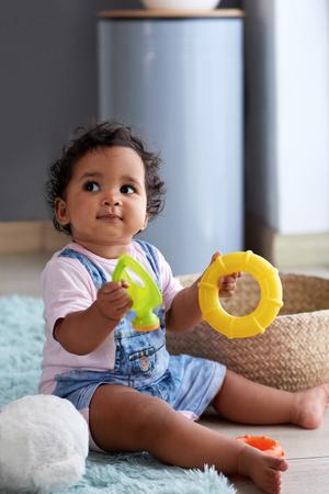 Young baby girl playing with toys at home in nursery with copy space, childhood development and curiousity Banco de Imagens