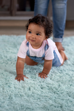Baby girl crawling around on carpet, learning how to move walk babyhood development movement Banco de Imagens