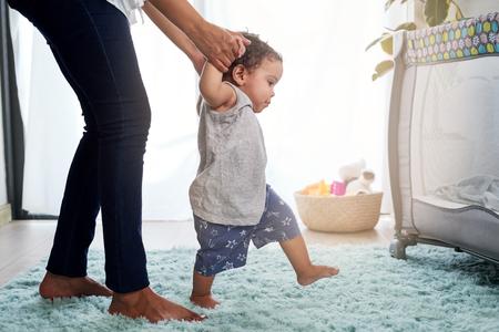 Primeros pasos del bebé tomados de la mano de la madre, lindo caminar inestable en casa vivero con cuna