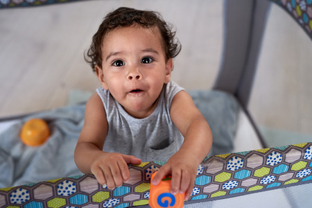 Portrait of cute baby boy in cot holding a toy block, childhood development educational Banco de Imagens