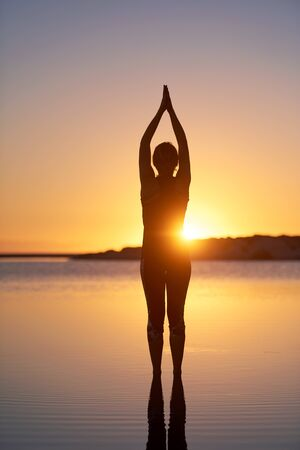 Woman practicing yoga at the beach during sunrise Stok Fotoğraf