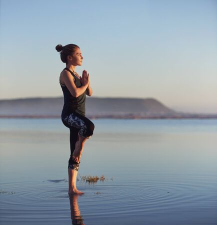 Woman blancing in yoga pose at the beach for a healthy lifestyle Stok Fotoğraf