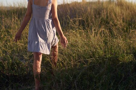 Woman walking with hands out in long grass at the beach Stok Fotoğraf