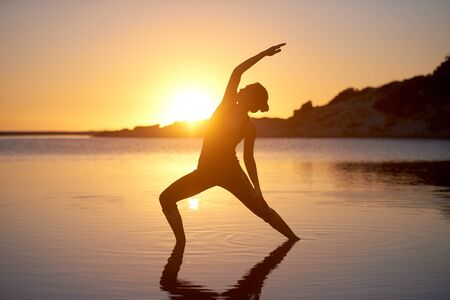 Yoga stretch woman silhouette at the beach healthy welness concept