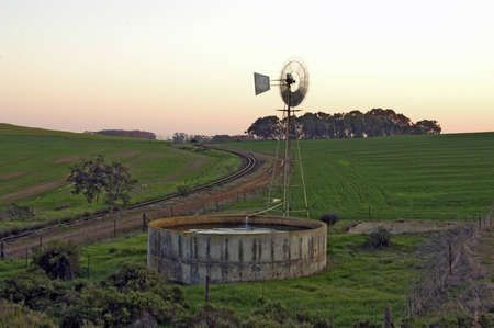 farm windmill spinning next to dam with train track alongside