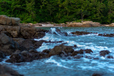 the sea near the jungle. a few rocks in the middle of the sea with sea waves Stok Fotoğraf