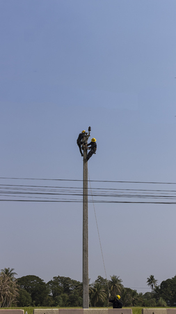 men install electric cable on high ground