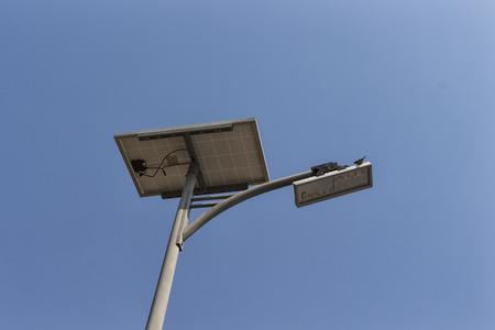Panneau solaire et lampadaire LED sur le ciel bleu et un oiseau Banque d'images - 73253654