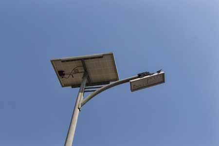 pannel: solar pannel and  LED street lamp pole on blue sky and a bird Stock Photo