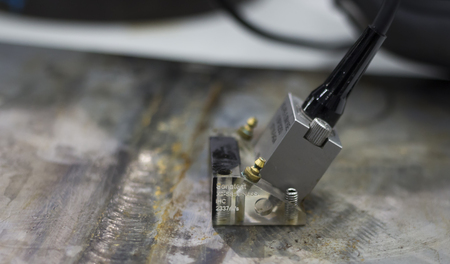 close up ultrasonic probe inspecting metal plate to find defect