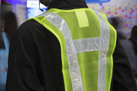 The back of a yellow mesh safety vest with reflective tape. Stock Photo