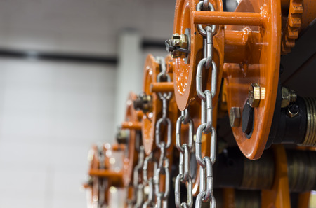 Industrial Steel Chains in orange hoists ; Selective focus