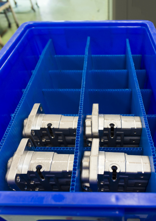 Automotive Aluminium parts kept in a blue plateic box ; parts produced by Low Pressure Die casting process and cnc machining machine Stock Photo